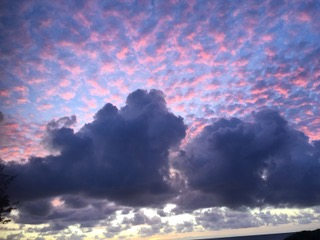 Kauai sunset with small clouds sprayed across sky in pinks and purples.